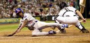 Delino DeShields of the Chicago Cubs slides safetly across home plate following a double by Sammy Sosa in the seventh inning. Brad Ausmus is the Houston catcher. The Cubs whipped the Astros, 6-2, Monday in Houston.
