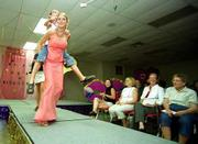 CLinton Eagles' Kaylee Wempe carries Alissa Freeman down the isle during the 4-H Fashion Revue. Young men and women flaunted flashy clothing during the event Friday at the Douglas County 4-H Fairgrounds.