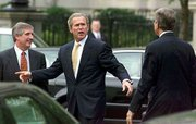 President Bush talks with Sen. Trent Lott, R-Miss, right, as he walked to the White House. Bush on Thursday discussed his travails in working with Congress, but insisted that his legislative agenda is being accomplished. Walking with Bush is Andy Card,left, his chief of staff.