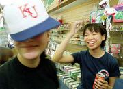 Twenty students from Hiratsuka, Japan, one of Lawrence's sister cities, are visiting this week as part of an exchange program. Niki Smith, 15, Lawrence, left, tries on a Kansas University hat for Chie Watanabe, 13, Hiratsuka, as the two shopped Thursday at Jayhawk Spirit, 935 Mass.