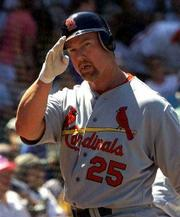 MARK MCGWIRE WAVES to the crowd after hitting the first of his two home runs Thursday at Wrigley Field. The Cardinals defeated the Cubs, 3-1.