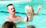 Getting a chance to splash dad is all part of the lesson, and Holly Swearingen, 3, relishes the moment.