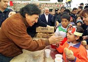 Peru President Alejandro Toledo, left, gives bread to a girl in a school in a shantytown in Lima. Toledo, Peru's first freely elected president of Indian descent, was sworn into office Saturday, promising to remain true to his roots and govern for the nation's poor majority.