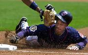 Cleveland's Kenny Lofton is tagged out at first base on a pickoff move by Detroit pitcher Victor Santos. That's the glove of Tigers' first baseman Tony Clark. The Indians and Tigers divided a twinbill on Saturday in Detroit.