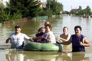 A mother and her children are evacuated in a rubber boat in the flooded village of Sokolniki, southern Poland. Workers on Monday evacuated villages ahead of a 65-mile-long flood wave coursing down the Vistula River.