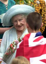 Britain's Queen Mother Elizabeth receives a bouquet of flowers from a youth wrapped in a Union Jack flag during the queen mum's 101st birthday celebration. Thousands of Britons gathered to honor her Saturday outside her residence.