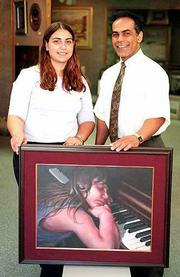 """Maryam Zangeneh and her father, Mehrzad Alison, hold a portrait by Alison called """"Late Night."""" The painting shows a young Zangeneh tired of practicing her piano."""