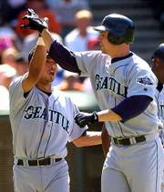 Seattle's Dan Wilson, right, gives a high-five to teammate Carlos Guillen. Wilson hit a three-run home run in the Mariners' 8-5 win over the Indians on Saturday in Cleveland.