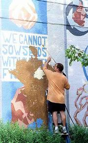 "The ""Seeds"" mural on the east wall of the former Community Mercantile, 9th and Mississippi and painted by Dave Lowenstein, Sandy Broughton and friends in December of 1996, is removed from the building. Tuesday John Patchen with Johnson Construction, Lawrence, power washes paint off the building which will be the location for a new Cork and Barrel Wine and Spirits store. Several neighbors and passersby were upset to see the colorful mural being removed."