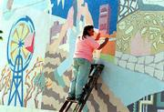 "In this file photo from October, 1996, artist Sandy Broughton paints in a scene on the ""Seeds"" mural on the east wall of the former Community Mercantile at 9th and Mississippi. Tuesday workers began removing a part of the mural with a power washer and Wednesday the mural is to be painted over. Cork and Barrel is opening a store in the building."