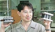 Trung Van Nguyen, associate professor of chemical and petroleum engineering at Kansas University, holds a single fuel cell, left, and a fuel cell stack. He predicts that the new energy source he is helping develop will replace the fossil fuel industry in 25 years to 100 years.