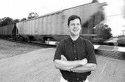 Railroad crossing safety is getting the attention of researchers at Kansas University. Stephen Lohmeier, an assistant professor of electrical engineering and computer science, is working with officials at Union Pacific Railroad on a $121,000 contract. Lohmeier is pictured with a speeding freight train at the Laptad crossing north of Lawrence.