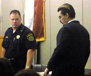 Dallas County Deputy Sheriff Greg Fisher watches as George Rivas enters court for his trial. Rivas, whose trial began Monday, is one of six convicts accused of killing Irving Officer Aubrey Hawkins on Christmas Eve, two weeks after they broke out of prison. A seventh escapee committed suicide.