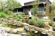 Craig Van Blaricum adds some mulch to a landscaping area outside the new Stone Canyon, 3801 W. Sixth St. The restaurant is scheduled to open for dinner and drinks Aug. 27.