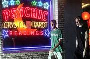City officials say businesses like the Lawrence Metaphysical Shop should be legal, despite laws on the books that say otherwise. Wes Meyer, left, and Brett Kerr on Friday strolled past the Shop at 1017 Mass., which provides palm, Tarot card and crystal readings.