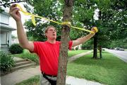 Longtime Oread neighborhood resident Tom Argiro secures a ribbon around a tree in opposition to Kansas University's encroachment into the Oread neighborhood. KU's plan to raze the 1300 block of Ohio to make way for two scholarship halls sparked protest earlier this summer from Oread residents. City and KU officials are now working on an agreement to allow for joint decision-making.