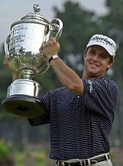 David Toms hoists the walker trophy after winning the PGA Championship. Toms sank a 12-foot putt on the 18th green to secure his first major title and deny Phil Mickelson on Sunday in Duluth, Ga.