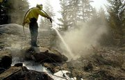 Firefighter Thomas Velasquez of Hungry Horse, Mont., sprays foam on hot spots on the property of Bill Schmidt along Icicle Ridge near Leavenworth, Wash. Schmidt's home and workshop were saved Sunday, but his van was destroyed. Fires in the Icicle complex have burned 6,500 acres and are being fought by 810 firefighters.