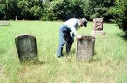 Henry Flory looks at the tombstone of Jacob Ulrich in the Ulrich Cemetery nine miles south of Lawrence. Ulrich's home was burned by Quantrill's raiders in 1863 and he died the following December at the age of 60.