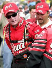 Dale Earnhardt Jr. puts on a head-and-neck-restraint system prior to the Pepsi 400. Earnhardt used the device for the first time over the weekend at the Michigan International Speedway in Brooklyn, Mich.