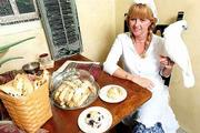 Every morning, Karen Wagner bakes fresh biscotti and scones for four Lawrence businesses. Her husband, Orlin, started the home-based business O&K Kitchen in the early 1990s. Karen Wagner displays a few of her products with the assistance of her bird, Maxi, who doesn't help with the cooking.