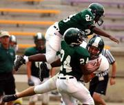 Free State's Brandon Jackson, top, and Damienn Patton (24) converge on Joe Sicilian. Sicilian's White team lost to the Greens, 13-0, on Wednesday at Haskell Stadium.