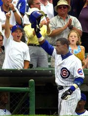 Chicago's Sammy Sosa waves to the crowd at Wrigley Field after hitting his third home run of the game. The Cubs clobbered Milwaukee, 16-3, Wednesday as Sosa increased his home run total to 49 this season.