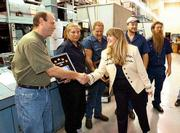 "Steve Campbell, direct to plate supervisor for the Lawrence Journal-World&squot;s USA Today production team, accepts congratulations from Lori Craig, director of field operations for USA Today. The Lawrence team received the ""Top Printsite"" award Thursday night at the Journal-World. Joining Campbell are, from left, coworkers Keri Collins, Steve Meeker, Gary Ellison and Ed Kelly.v"