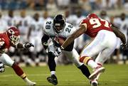 Jacksonville running back Fred Taylor slices between Kansas City's William Bartee, left, and Rich Owens. KC lost, 28-23, Thursday night in Jacksonville, Fla.