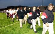 Lawrence High football coach dirk wedd leads his team off the field after the Lions' game against Shawnee Mission East was postponed by lightning. Thursday night's game at Overland Park was rescheduled for 11 a.m. Saturday at Shawnee Mission South District Stadium.