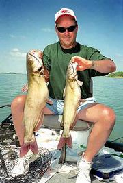 David schmidtlein holds a couple of channel catfish he caught and released at Melvern Lake.