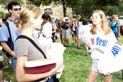 AUTUMN FENSTERLE, right, passes out T-shirts as part of the KU First capital campaign to be kicked off this week at Kansas University. Students wearing the shirts to Saturday's KU-UCLA football game can get in for free and are eligible to win one of 25 $1000 scholarships.