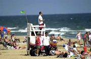 Capt. Robert Lindauer, a veteran lifeguard for Sandbridge Ocean Rescue, keeps an eye on swimmers in Virginia Beach, Va. The governor of Virginia announced Wednesday the creation of a task force to study a pair of fatal shark attacks over Labor Day weekend.