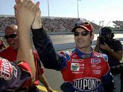 Jeff Gordon high-fives a crew member after winning the pole position for the Monte Carlo 400 Friday in Richmond, Va.
