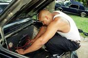 Carlos Dahda perches in the trunk of his 1986 Oldsmobile Cutlass