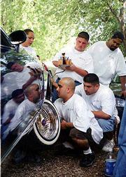 "David ""junior"" jones, top center, gently manipulates the hydraulic controls to his 1983 Buick Regal low rider as Anthony ""Chico"" Reyes Jr., bottom center, and Tony Garcia, bottom right, repair a hydraulic cylinder in the car&squot;s wheel well. The men were among more than two dozen members of the 4GOTN1s car club who recently gathered at Garcia&squot;s North Lawrence home for a cookout and a chance to show off and work on their cars."