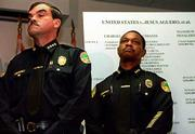City of Miami Police Chief Raul Martinez, left, and Deputy Chief Bobby Cheatham listen to U.S. attorneys during a news conference discussing indictments against 13 current and former officers. All of those charged Friday were veterans assigned to SWAT teams, narcotics units or special crime-suppression teams in the late 1990s.