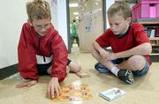 """Three Lawrence elementary schools, including Langston Hughes School, met the standard of excellence in state math assessments. Friday at Langston Hughes, fifth-grade students Kevin Brady, left, and Shawn Strutt, play """"The Crazy Plane Game"""" during a math period."""
