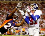 New York wide receiver Amani Toomer, right, pulls in a 43-yard touchdown pass ahead of Denver safety Kenoy Kennedy. The Broncos beat the Giants, 31-20, on Monday in Denver.