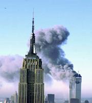 Plumes of smoke pour from the World Trade Center buildings in New York Tuesday, Sept. 11, 2001. Planes crashed into the upper floors of both World Trade Center towers minutes apart Tuesday in a horrific scene of explosions and fires that left gaping holes in the 110-story buildings. The Empire State building is seen in the foreground.