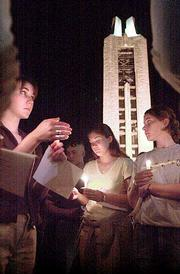 Mara Richards, from left, Cindy Riggins and Lana Seibel huddle together holding candles in remembrance of victims in Tuesday's terrorist attacks on the United States. Richards, Riggins and Seibel were among an estimated 1,000 people that gathered for a vigil Thursday near the Campanile at Kansas University, according to university spokeswoman Lynn Bretz.
