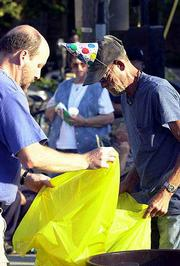 Brent Lamb, left, father of Emily Lamb, who organizes birthday parties for the Lawrence homeless, helps Eugene Coffelt take out the trash during a barbecue party at the Community Drop In Center, 214 W. 10th St. The center tied the celebration of Emily's 12th birthday Thursday with a community party, offering free food and music to the public.