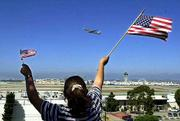 Rebecca Arellano of Hawthorne, Calif., waves a pair of American flags from an overlook in El Segundo, Calif., as a jetliner takes off from Los Angeles International Airport. It was the first plane to leave the airport Thursday.