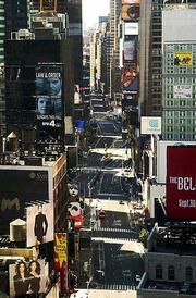 Times Squate remains nearly deserted as afternoon approaches. On Wednesday, the normally bustling car and foot traffic on Broadway through Times Square was almost non-existant.