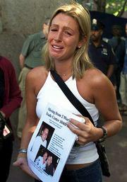 Rachel Uchitel makes an emotional plea as she searches for her fiancJames Andrew O'Grady, outside Bellevue Hospital in Manhattan. O'Grady was working on the 104th floor of Tower 2 of New York's World Trade Center when it was destroyed Tuesday.