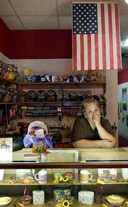 "Becky Bowers placed a flag above the gift area of her store at Penny Annie&squot;s Sweet Shoppe, 845 Mass. ""I just thought it would be a good idea if everyone would put one out to show their support,"" she said Thursday, minding the store and listening to the news on radio."