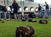 A baseball glove lies in the grass at Enron Field while the San Francisco Giants stretch. San Francisco's game Thursday at Houston was postponed because of the national tragedy. Baseball won't resume play until Monday.