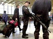 Massachusetts State Police troopers armed with automatic weapons patrol the terminal at Logan International Airport in Boston. Logan, where two of Tuesday's hijacked flights originated, reopened Saturday with increased security in the aftermath of the terrorist attacks on U.S. targets.