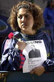 Lorena Ocampo holds a flier with a photo of a missing friend that she hands out at the 69th Regiment Armory in New York. The armory continued Saturday to serve as a center for people to gather who are searching for information on loved ones missing since Tuesday's terrorist attack on the World Trade Center.