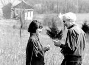 "Joan and Harris Stone stand in a field near Barber School at Clinton Lake. Joan said the photo represents her and her late husband as distinct individuals but also as one, like ""a singular blade of grass."" Harris led a project to restore Barber School, shown at upper left."